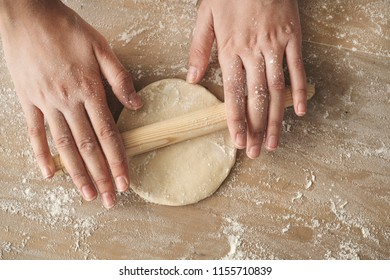 Female hands rolling dough on wooden table