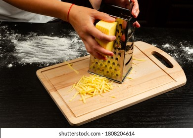 female hands rubbing fresh cheese on a grater on a wooden cutting board