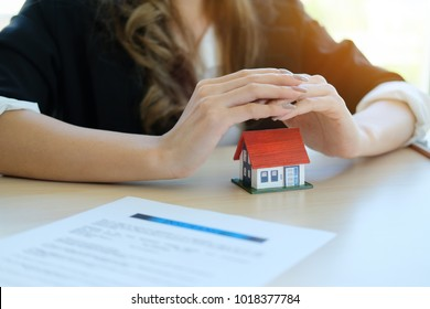 Female hands saving small house with a roof - architecture, safety, security, real estate and property concept - close up of hands protecting house or home model
