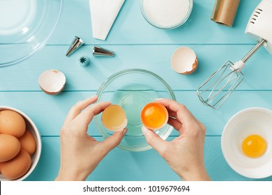 Female hands separate egg white from yolk for whipped cream. Step by step recipe of meringue with ingredients and utensils. Flat lay.