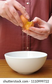 Female hands separate the egg white from the yolk over a bowl in the kitchen