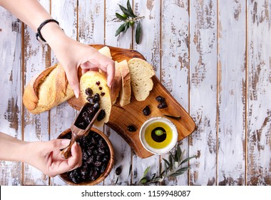 Female hands serving traditional Greek Appetizer olives with bread, olive oil  and balsamic vinegar, over rustic olive wooden board over a white wooden background. Top View