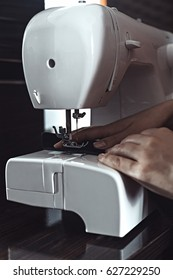 Female hands sew on a sewing machine