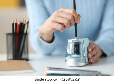 Female hands sharping pencil with electronic sharpener closeup