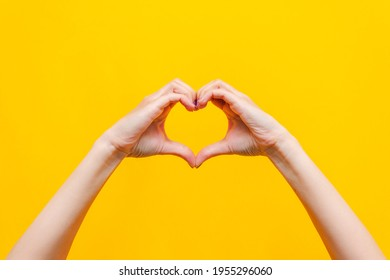 Female hands showing a heart shape isolated on a bright color yellow background. Sign of love, harmony, gratitude, charity. Feelings and emotions concept - Shutterstock ID 1955296060