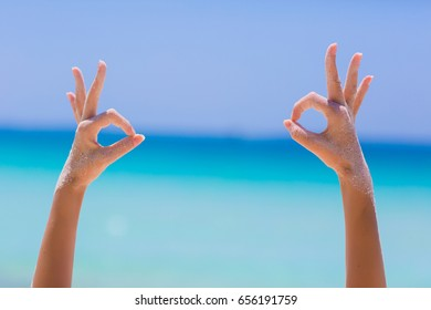 Female hands showing ok sign on blue sea background