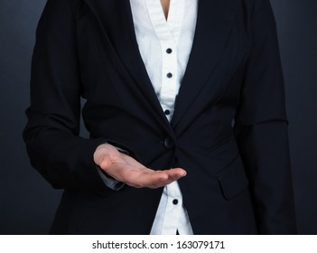 Female hands showing something on grey background