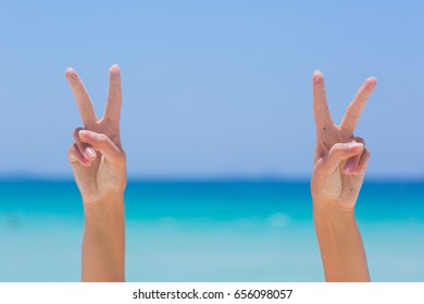 Female hands showing victory sign on blue sea background