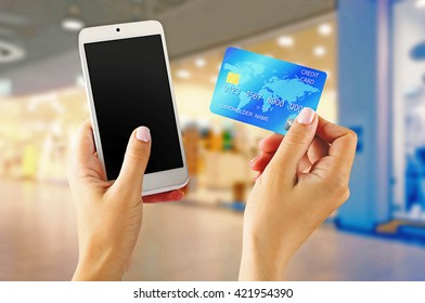 Female hands shows mobile smart phone and credit card, blurred background
