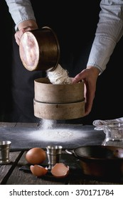 Female hands sifting flour from old sieve on old wooden kitchen table. Vintage kitchenware with flour, water and eggs at foreground. Dark rustic style.