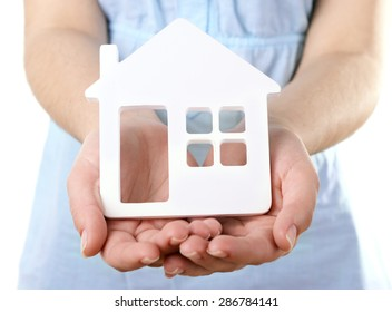 Female hands with small model of house isolated on white