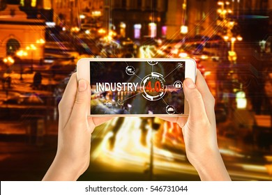 Female hands with smartphone on cityscape background. Text INDUSTRY 4.0 on screen
