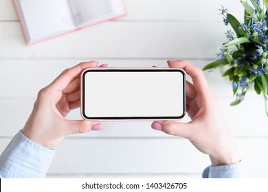 Female hands with a smartphone. White blank screen. Table with notebook and flowers on background