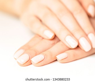 Female hands with smooth skin and stylish beige pastel manicure.