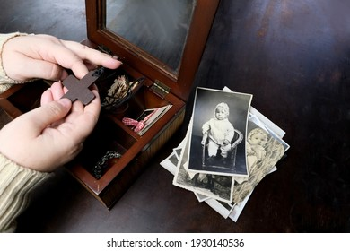 female hands sorting dear to heart memorabilia in old wooden box, stack of retro photographs, wooden cross, vintage photographs of 1960, concept of family tree, genealogy, childhood memories