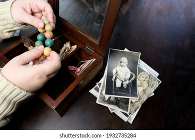 female hands are sorting dear to heart memorabilia in an old wooden box, a stack of retro photos, a wooden rosary, vintage photographs of 1960, concept of family tree, genealogy, childhood memories