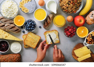 Female hands spreading butter on bread. Woman cooking breakfast. Healthy breakfast ingredients, food frame. Granola, egg, nuts, fruits, berries, milk, yogurt, juice, cheese. Top view, copy space.
