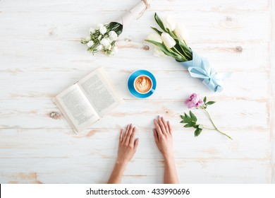 Female hands spreading over wooden table with flowers
