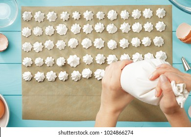 Female hands squeeze whipped cream on baking paper. Step by step recipe of meringue cookies. Process of meringue making top view.