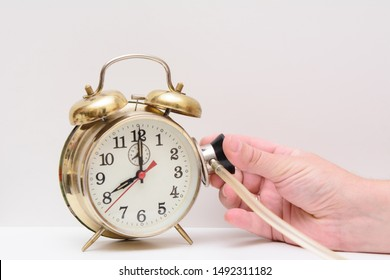 In female hands a stethoscope. The doctor pressed a stethoscope to the surface of the alarm clock. Concept - heart disease. Spoiled time. Listen to the heart, time.