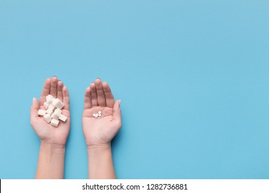 Female hands with sugar and pills on blue background. Choice of sweetener in tablets or regular sugar. Alternative to sugar for diabetics.