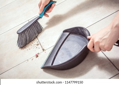 Female Hands Sweeping Dust With A Broom On A Dustpan, Housekeeping Concept