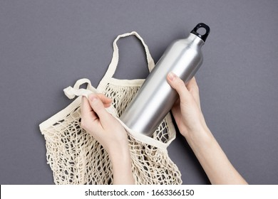 Female hands take metal bottle from string bag. Zero waste concept on dark gray background.