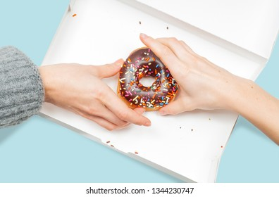 Female hands is taking colorful donuts. Hands is grabbing last donuts in box on pastel blue background.