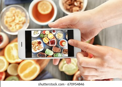 Female hands taking pictures of breakfast on table
