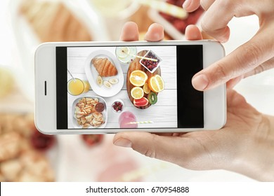 Female hands taking pictures of tasty breakfast on table