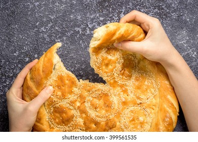 female hands, tearing a loaf of white bread with sesame with copy space
