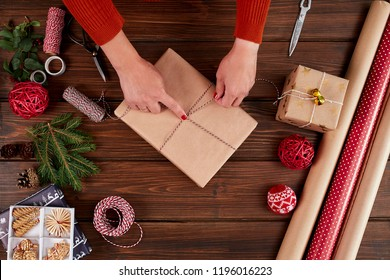 Female hands tie a unprepared gift wrapped in kraft paper with string, modern eco-friendly christmas packaging ideas, close up. Wrapping inspiration. Christmas presents, packaging Concept
