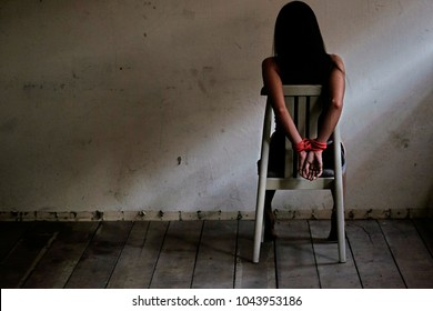 Female hands tied up with rope, bound hands, young woman sitting on chair and  tied up with rope