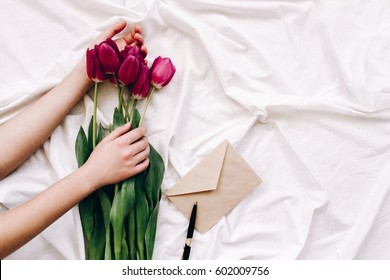 Female hands touch the red tulips on the sheet with folds. An envelope and a pen. Spring flowers in bed. top view