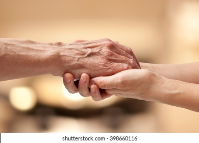 Female hands touching old male hand - taking care of the elderly concept