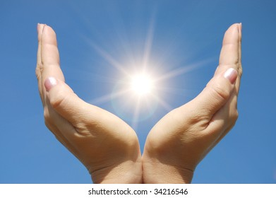 Female hands touching the Sun