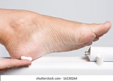 Female hands treating dry feet with moisturizing cream