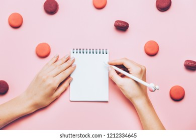 Female hands with trendy manicure writting in empty note book on pink background with many macaroons. Top view, flat lay. Mock up template. Blogger working process