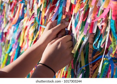 Female hands tying colored ribbons on grid in front of Bonfim church in Salvador, Bahia, Brazil