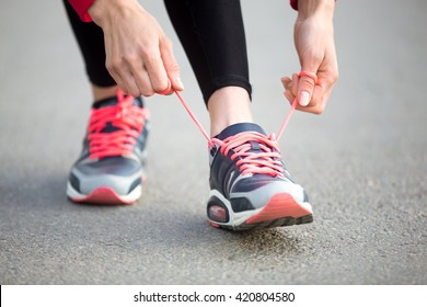 Female hands tying shoelace on running shoes before practice. Woman athlete preparing for jogging outdoors. Runner getting ready for training. Sport active lifestyle concept. Close-up
