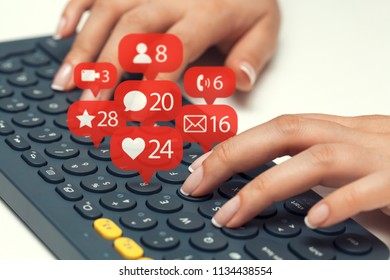 female hands typing on keyboard and notification icons of social network flying over keyboard
