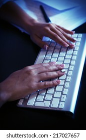 Female hands typing on keyboard, close-up, on dark background