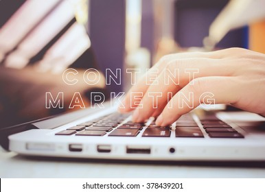 Female hands typing on keyboard of laptop with content marketing word