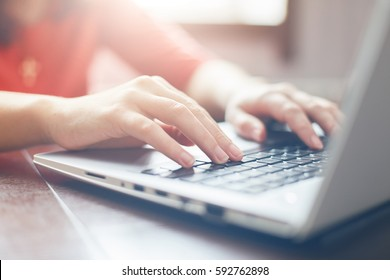 Female hands typing on keyboard of laptop surfing Internet and tex-ting friends via social networks, sitting at wooden table indoors. Technology and communication concept Selective focus.