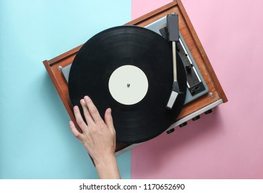 Female hands  use retro vinyl player on a blue pink pastel background. DJ. Top View