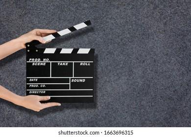 Female hands using classic film clapperboard