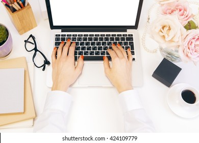 Female hands using laptop with blank white screen on designer desktop with flowers, coffee, glasses and other items. Top view, Mock up