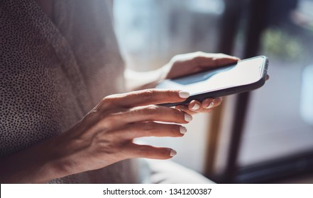 Female hands using mobile phone at sunny day in workplace.Horizontal. Blurred background