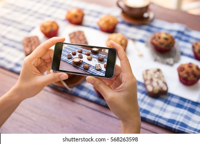 Female hands using mobile phone taking photo of bakery, brownies and cakes on the table.