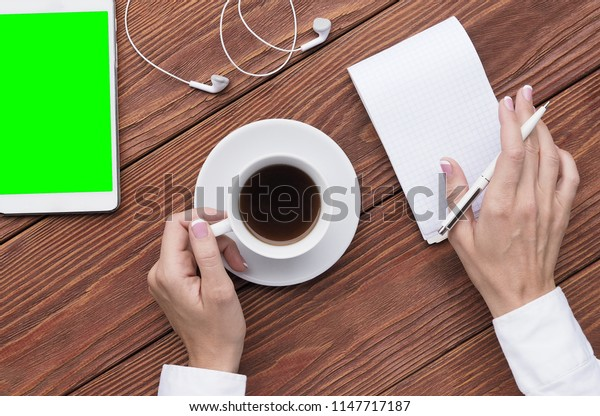 Female hands using notepad and cup of coffee, mockup digital tablet and headphones on brown wood desk, top view.